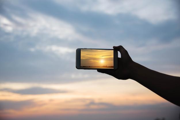 Schattenbildhand, die smartphone hält foto im sonnenuntergang machen.
