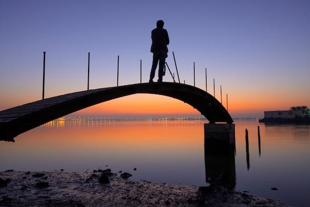 Schattenbildholzbrücke erlöschen zum wasser mit dem fotografmann, der foto über buntem sonnenaufganghimmel- und -stadtlichthintergrund machend steht.