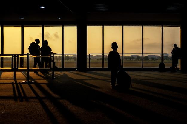 Schattenbildjunge im flughafenabfertigungsgebäude am sonnenaufgang