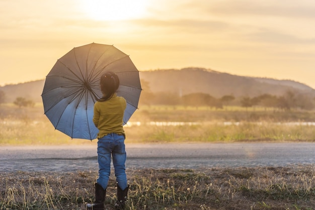 Schattenbildkinder mit regenschirm bei sonnenuntergang
