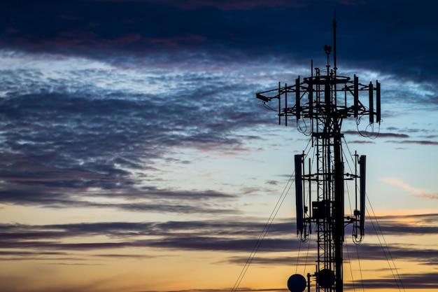 Schattenbildkommunikations-turmpfosten auf sonnenunterganghintergrund