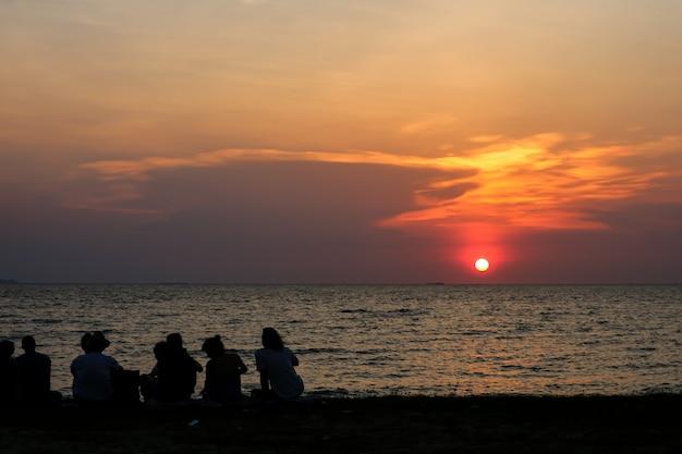 Schattenbildleute, die blicksonnenunterganghimmel auf strand treffen