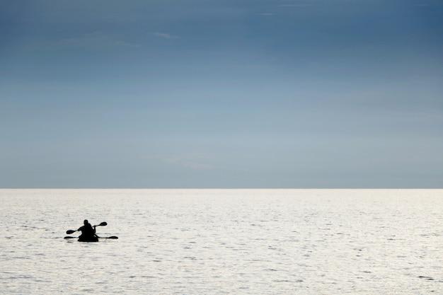Schattenbildleute, die im urlaub kanuboot in der seezeit für boot fahren, entspannen sich bei teay ngam beach