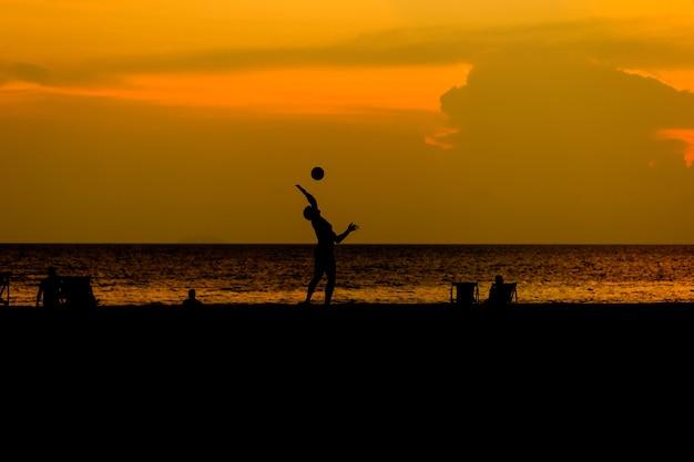 Schattenbildleute spielen strandvolleyball.
