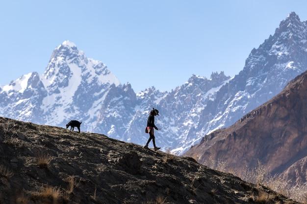Schattenbildmädchen, das in den bergen geht