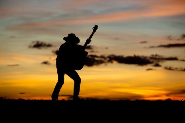 Schattenbildmädchengitarrist auf einem sonnenuntergang