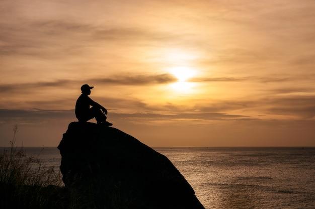 Schattenbildmann, der auf großem felsen mit besichtigung des sonnenuntergangs im tropischen meer sitzt