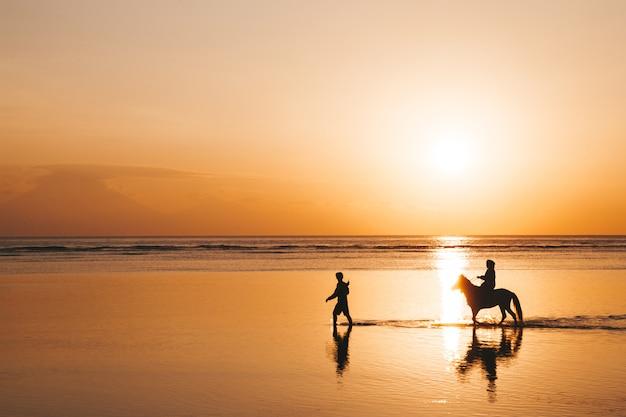 Schattenbildporträt des jungen romantischen paares, das auf dem pferderücken am strand reitet. mädchen und ihr freund am goldenen bunten sonnenuntergang