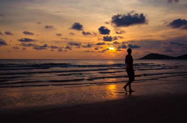 Schattenbildsonnenuntergang mit dem mädchen, das auf strand geht