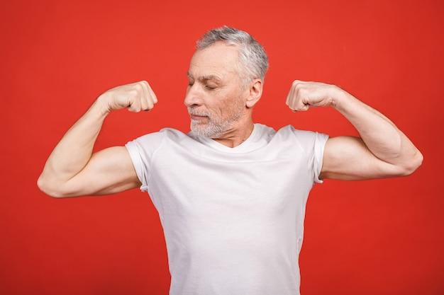 Schau dir das an! älterer mann, der muskel zeigt. alter mann, der seine arme isoliert beugt. fröhlicher aufgeregter moderner cooler rentner-opa, der bodybuilding übt.