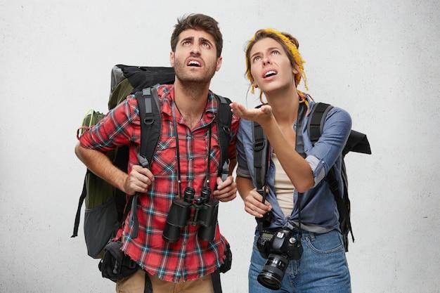 Schau dir das an! erstaunte frau mit rucksack und kamera, die ihrem ehemann etwas mit der hand zeigt, zusammen geschockt, isoliert. junge reisende mit schockiertem blick