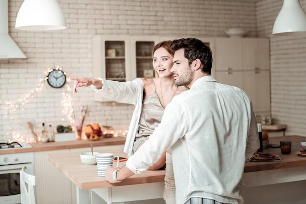 Schau dir das an. lächelnde junge langhaarige hübsche frau in einem weißen hemd, das auf das fenster zeigt, während sie auf dem tisch sitzt
