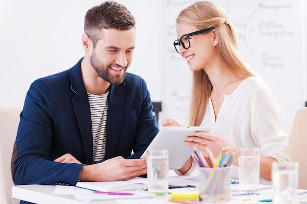 Schau dir das einfach an! zwei selbstbewusste geschäftsleute in eleganter freizeitkleidung, die zusammen am tisch sitzen und etwas diskutieren, während sie auf das digitale tablet schauen