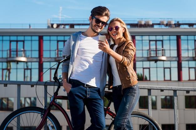 Schau dir dieses foto an! schönes junges paar, das auf das handy schaut und lächelt, während es draußen in der nähe des fahrrads steht
