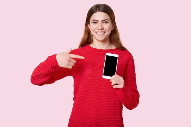 Schau dir dieses gadget an. glücklich lächelnde europäische junge frau zeigt auf modernes handy mit leerem bildschirm für ihren werbeinhalt