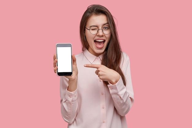 Schau dir dieses handy an! erfreute glückliche frau blinzelt augen, zeigt mit dem zeigefinger auf leeren bildschirm, zeigt modernes gerät