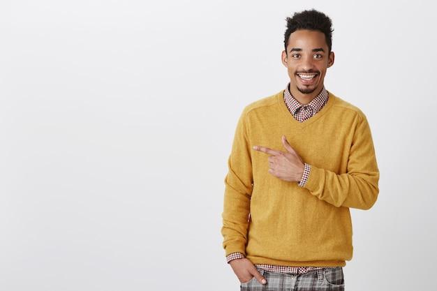 Schau dir dieses heiße mädchen an. porträt des glücklichen gutaussehenden afrikanischen mannes mit afro-haarschnitt im stilvollen gelben pullover, der nach links zeigt und positiv lächelt, zufrieden, interessantes konzept diskutierend