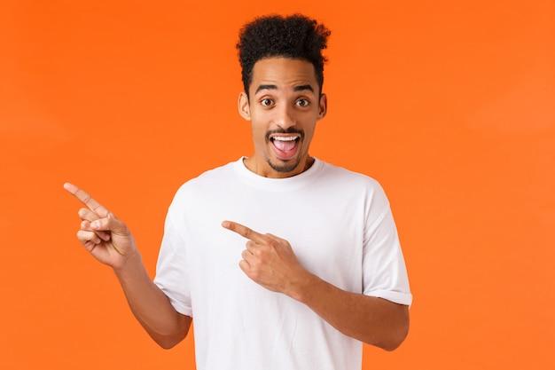Schau es dir an. unterhaltener und aufgeregter netter afroamerikanerhippie-kerl im weißen t-shirt, die obere linke ecke zeigend und lächeln, schlagen fantastischen platz vor, stellen das produkt vor, orange