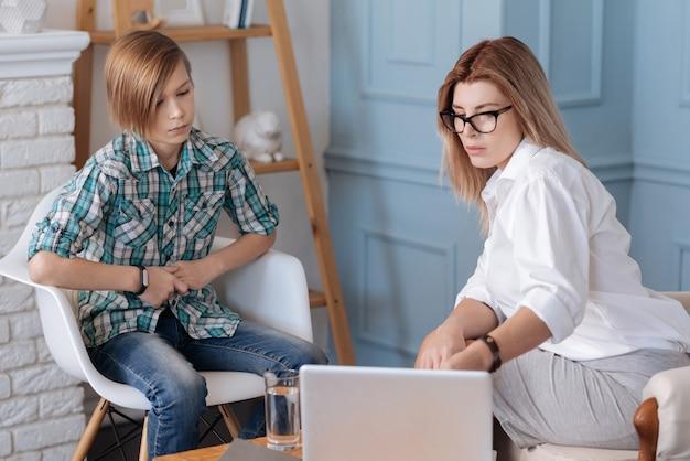 Schau hier. attraktive kluge psychologin, die eine brille trägt, die auf dem sofa sitzt, während bildschirm ihres computers zeigt