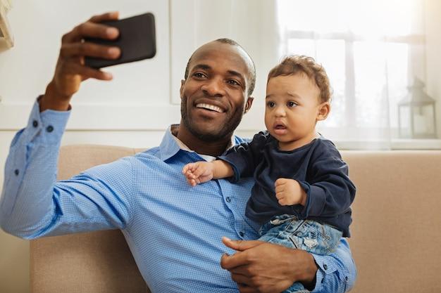 Schau hier. hübscher fröhlicher junger afroamerikanischer papa, der lächelt und seinen kleinen lockigen sohn hält, während er selfies nimmt