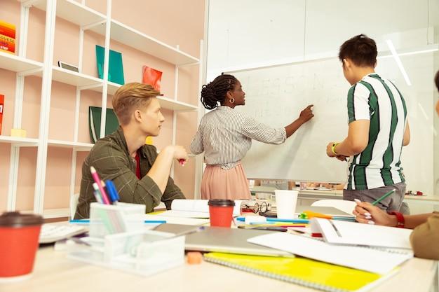 Schau hier. seriöser internationaler tutor, der in einer halben position steht, während er mit der gruppe in der sprachschule arbeitet