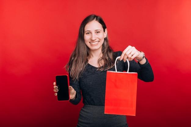 Schau, ich habe das online gekauft. glückliche junge frau lächelt in die kamera und zeigt eine einkaufstasche und ein mobiltelefon auf rotem raum.