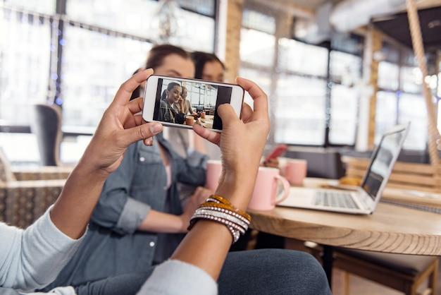 Schau in die kamera. schließen sie oben von den zarten weiblichen händen, die foto machen, während sie telefon halten und fokus einstellen