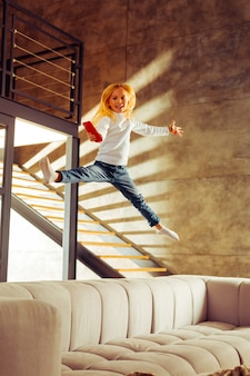 Schau mich an. fröhliches kind, das beim springen auf dem sofa ein lächeln im gesicht behält