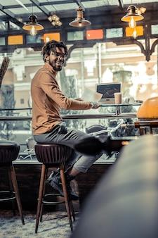 Schau mich an. hübsche männliche person, die lächeln auf seinem gesicht hält, während sie mit dokumenten arbeitet