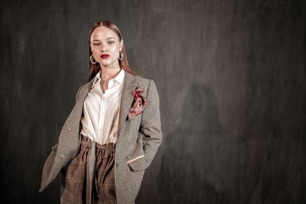 Schau mich an. professionelles model, das stilvollen mantel demonstriert und über grauer wand steht