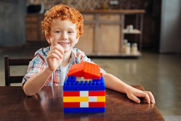Schau was ich gebaut habe. entzückender lockiger junge, der an einem tisch sitzt und aufgeregt wird, nachdem er seine arbeit an einem bunten plastikhaus zu hause beendet hat.