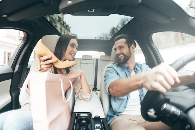 Schau, was ich habe! junges schönes paar, das auf den beifahrersitzen sitzt und sich ansieht, während eine attraktive frau ihrem freund neue schuhe zeigt