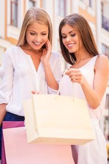 Schau, was ich habe! schöne junge frau, die ihrer freundin zeigt, was sie in ihrer einkaufstasche hat, während sie beide im freien steht