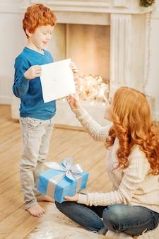 Schau was ich hier habe. aufgeregter kleiner junge, der seine mutter aufgeregt ansieht und ihr an einem weihnachtsmorgen ein neues meisterwerk zeigt.