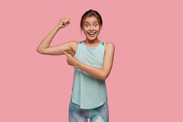 Schau wie stark ich bin! freudige junge frau mit breitem lächeln