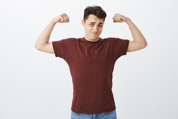 Schau wie stark ich bin. porträt des selbstsicheren gutaussehenden europäischen kerls im roten t-shirt