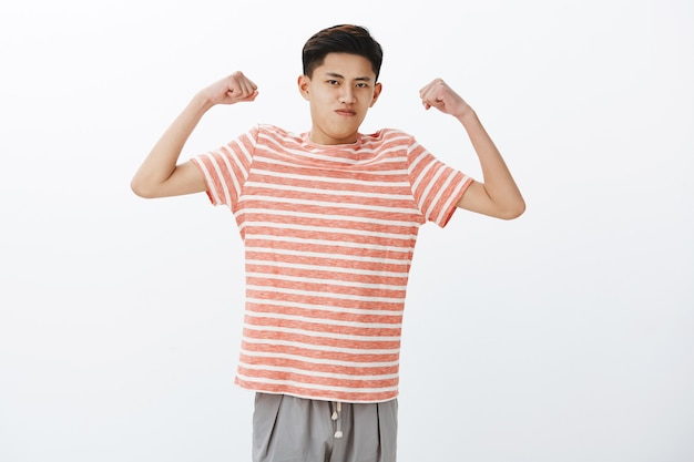 Schau wie stark ich bin. porträt eines selbstbewussten lustigen jungen schlanken asiatischen mannes, der hände hebt, um bizeps oder muskeln zu zeigen, die anfangen zu trainieren