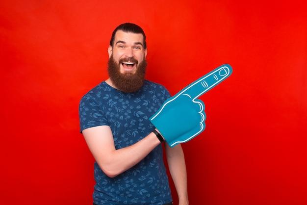Schaue auf meine linke. männlicher hipster trägt einen schaumfanhandschuh, der zur seite zeigt.