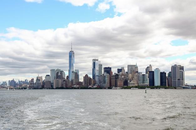 Schauen sie auf dem segelboot, das in den new- yorkhafengebäuden von manhattan-insel kreuzt