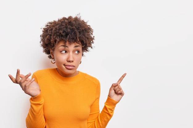 Schauen sie hier werben. verwirrt verwirrt dunkelhäutige lockige afro-amerikanerin hebt die handfläche hat anhaltspunkte, die oben auf dem kopierraum angezeigt werden, trägt einen lässigen orangefarbenen pullover isoliert über weißer wand
