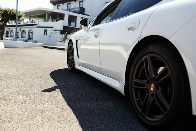 Schauen sie hinter weißem auto auf das weiße haus