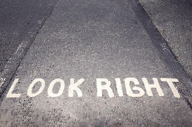 Schauen sie nach rechts warnung auf dem rollfeld in london, england, großbritannien, irland gemalt.