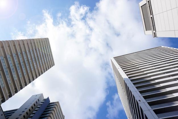 Schauen sie oben ansicht und ernte des bürogebäudes auf hellem hintergrund des blauen himmels. mit platz für texte