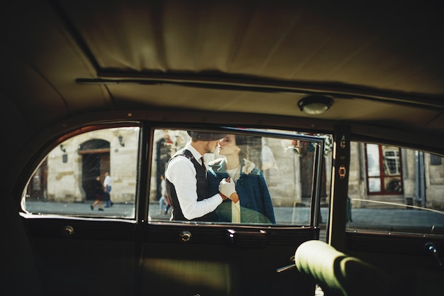 Schauen sie sich das retro-auto bei einem mann und einer frau im altmodischen stil an