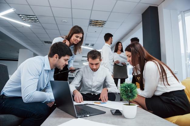 Schauen sie sich diese grafik an. eine gruppe junger freiberufler im büro unterhält sich und lächelt
