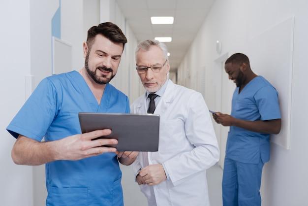 Schauen sie sich diese technische innovation an. beteiligte kompetente glückliche mediziner, die in der klinik stehen und tablette testen, während andere kollege ordner im hintergrund verwenden