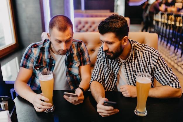 Schauen sie sich dieses foto an. zwei glückliche junge männer in freizeitkleidung trinken bier in der kneipe, während einer von ihnen smartphone hält und es mit einem lächeln zeigt