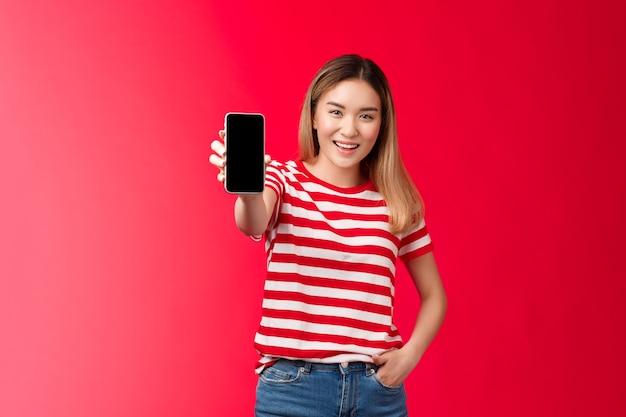Schauen sie sich meinen spielstand an sorglos gut aussehende blonde asiatische frau streckt den arm aus und zeigt den smartphone-bildschirm ...