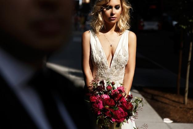 Schauen sie über die schulter des bräutigams um die braut, die mit rotem hochzeitsblumenstrauß im hellen sonnenschein steht