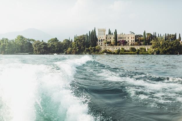 Schauen sie von einem boot aus auf ein wunderschönes anwesen am ufer. italien